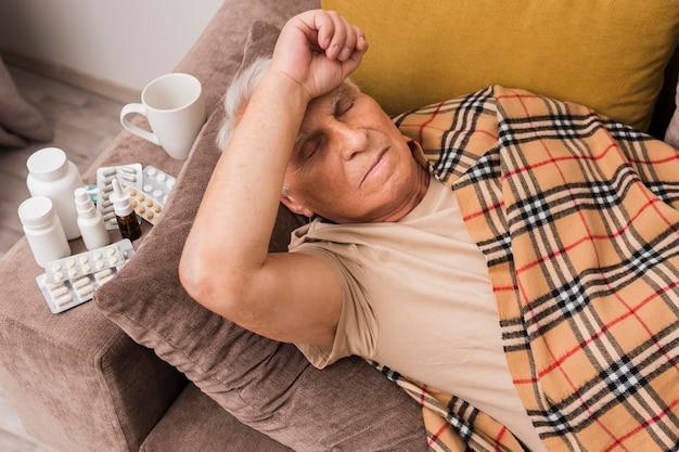 Wysoki kąt chory mężczyzna r. na kanapie