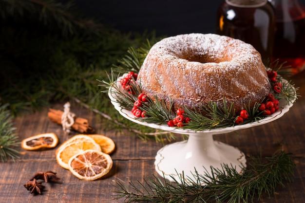 Wysoki kąt ciasta bożonarodzeniowego z czerwonymi jagodami i suszonymi cytrusami