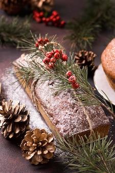 Wysoki kąt ciasta bożonarodzeniowego z czerwonymi jagodami i szyszkami