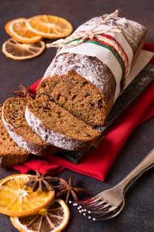 Wysoki kąt ciasta bożonarodzeniowego z widelcami i suszonymi cytrusami