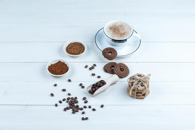Wysoki kąt ciasteczka, filiżankę kawy z miską kawy rozpuszczalnej, ziarna kawy na tle białej drewnianej tablicy. poziomy