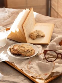 Wysoki kąt ciasteczka na tacy z książką i okularami