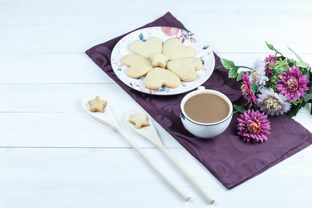Wysoki kąt ciasteczka w kształcie serca, filiżanka kawy na fioletowej podkładce z kwiatami
