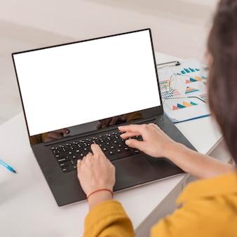 Wysoki kąt ciężarnej bizneswoman pracuje na laptopie