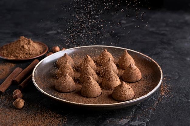 Wysoki kąt cukierki czekoladowe na talerzu z kakao w proszku