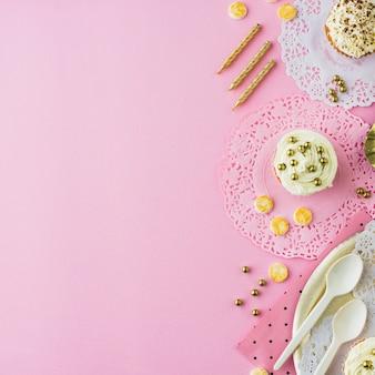 Wysoki kąt cupcakes; cukierki i świece na różowym tle
