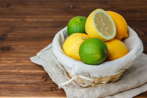 Wysoki kąt cytryny z koszem wypełnionym cytryną i połową cytryny na powierzchni drewnianych. poziomy