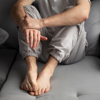 Wysoki kąt człowieka pozowanie podczas siedzenia na kanapie