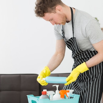 Wysoki kąt człowieka z koszem detergentów