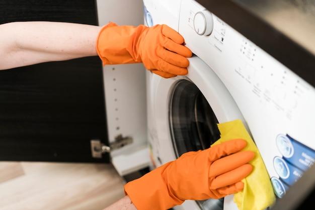 Wysoki kąt czyszczenia pralki przez kobietę