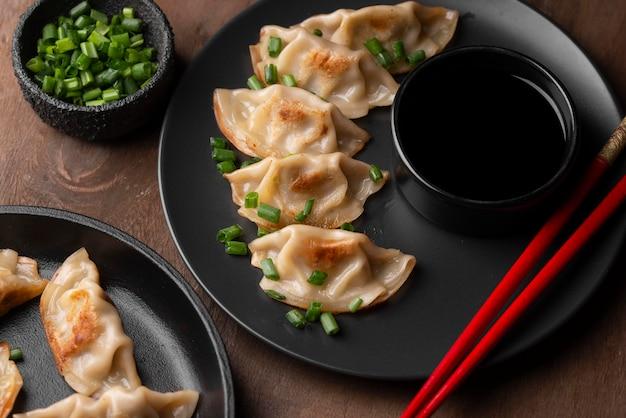 Wysoki kąt danie azjatyckie pierogi z pałeczkami i ziołami
