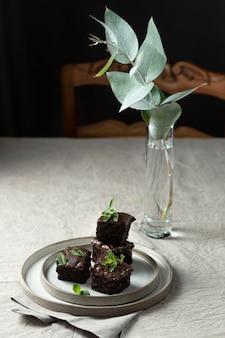 Wysoki kąt deser na talerzu z rośliną i wazonem