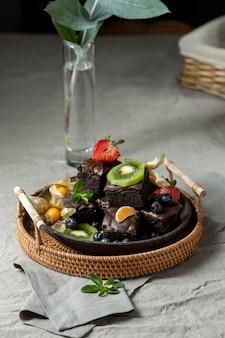 Wysoki kąt deserów owocowych na talerzu z wazonem i rośliną
