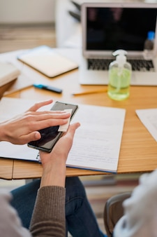 Wysoki kąt dezynfekcji smartfona przez kobietą przed zajęciami