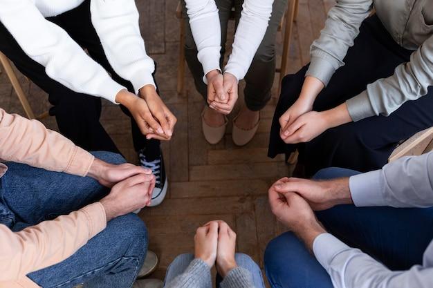 Wysoki kąt dłoni ludzi w kręgu na sesji terapii grupowej