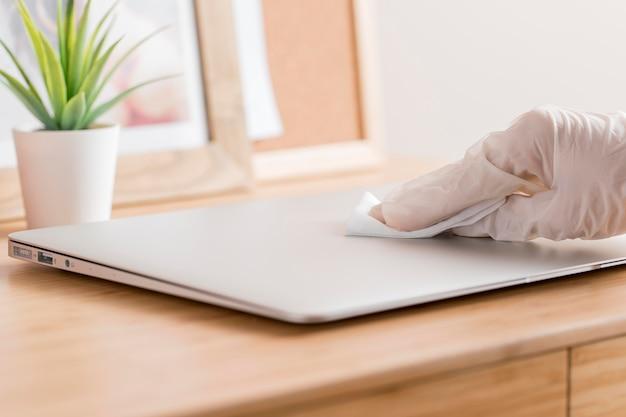 Wysoki kąt dłoni z dezynfekującym laptopem na rękawicy chirurgicznej na biurku