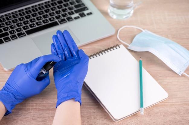 Wysoki kąt dłoni z rękawiczkami chirurgicznymi i środkiem odkażającym do rąk obok biurka
