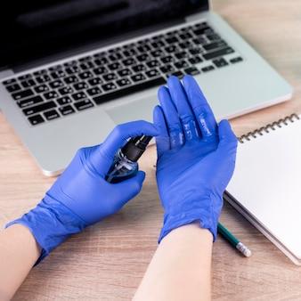 Wysoki kąt dłoni z rękawiczkami chirurgicznymi i środkiem odkażającym do rąk
