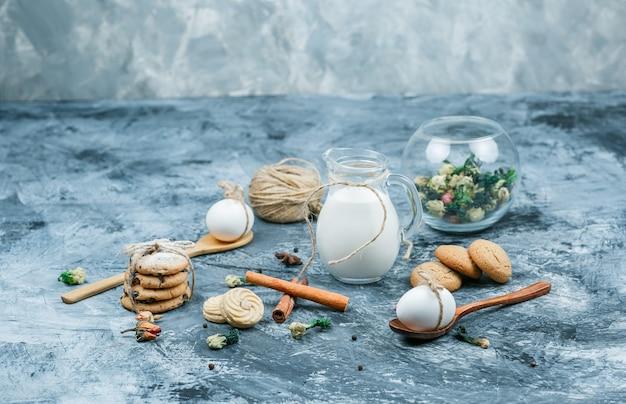Wysoki kąt dzbanek mleka i szklana miska jogurtu z łyżkami, ciasteczkami, jajami, szotami, cynamonem i rośliną na ciemnoniebieskim i szarym tle marmuru. wolne miejsce w poziomie na tekst