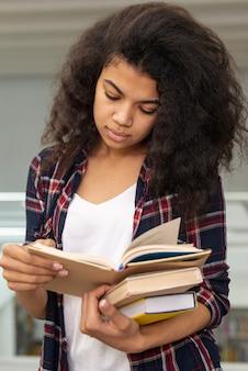 Wysoki kąt dziewczyna niosąca stos książek podczas czytania