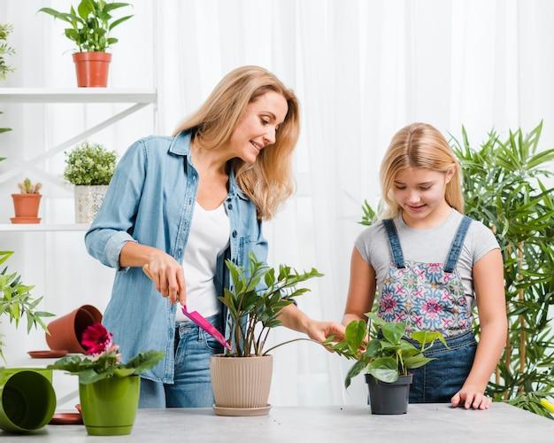 Wysoki kąt dziewczyna ogląda mama sadzenia kwiatów