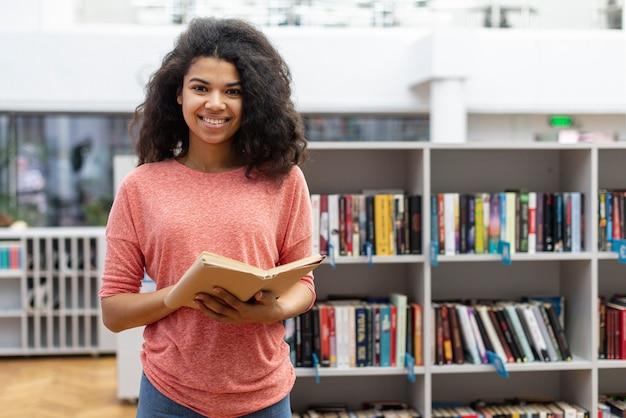 Wysoki kąt dziewczyna w bibliotece czytania