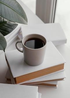 Wysoki kąt filiżanka kawy na książkach