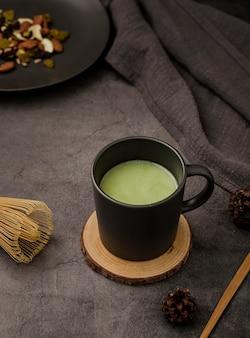 Wysoki kąt filiżanki herbaty matcha na podstawce