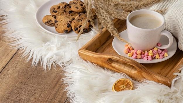 Wysoki kąt filiżanki kawy z ciasteczkami i suszonymi kwiatami