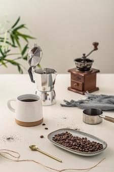 Wysoki kąt filiżanki kawy ze szlifierką na stole