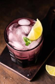 Wysoki kąt fioletowego szkła z mrożonym koktajlem z limonką
