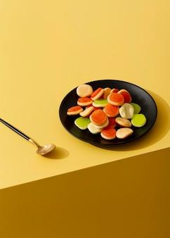 Wysoki kąt galaretki cukierki na talerzu z łyżeczką