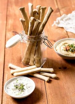 Wysoki kąt grissini w słoiku z sosem