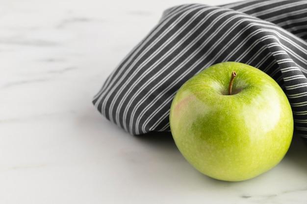 Wysoki kąt jabłka na stole szmatką