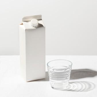 Wysoki kąt kartonu mleka z pustą szklanką