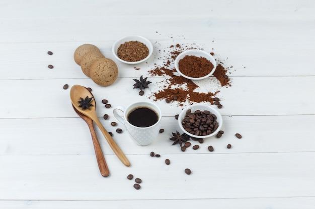 Wysoki kąt kawy w filiżance z ziaren kawy, kawa mielona, przyprawy, ciasteczka, drewniane łyżki na podłoże drewniane. poziomy