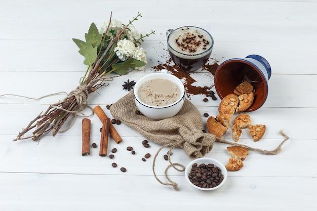 Wysoki kąt kawy w filiżankach z ziaren kawy, ciasteczka, kwiaty, laski cynamonu na tle drewnianych i worek.