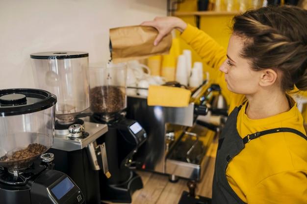 Wysoki kąt kobiecej baristy mielenia kawy