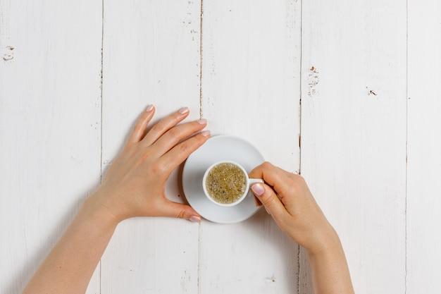 Wysoki kąt kobiecych dłoni trzyma filiżankę mocnej kawy