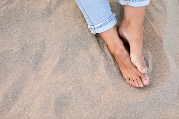 Wysoki kąt kobiecych stóp na piasku na plaży