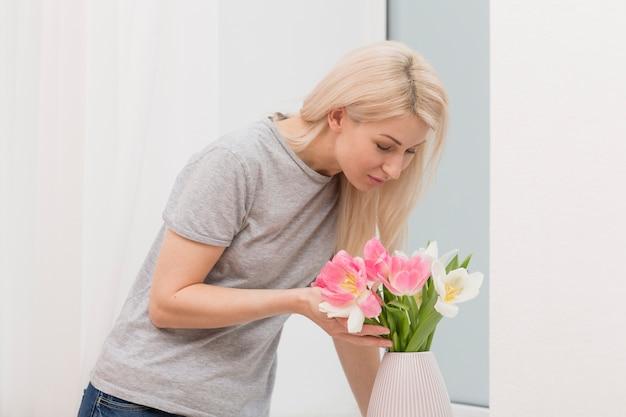 Wysoki kąt kobiet pachnące kwiaty