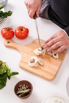 Wysoki kąt kobiet szefa kuchni cięcia grzybów