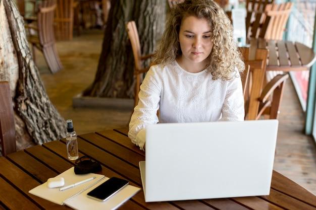 Wysoki kąt kobieta na tarasie, pracując na laptopie
