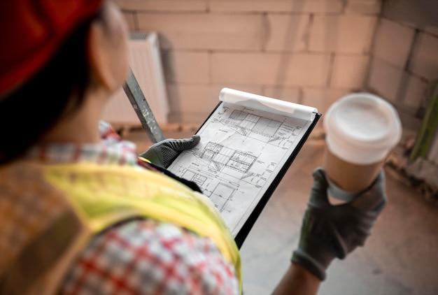Wysoki kąt kobieta pracownik budowlany trzyma kawę i plan