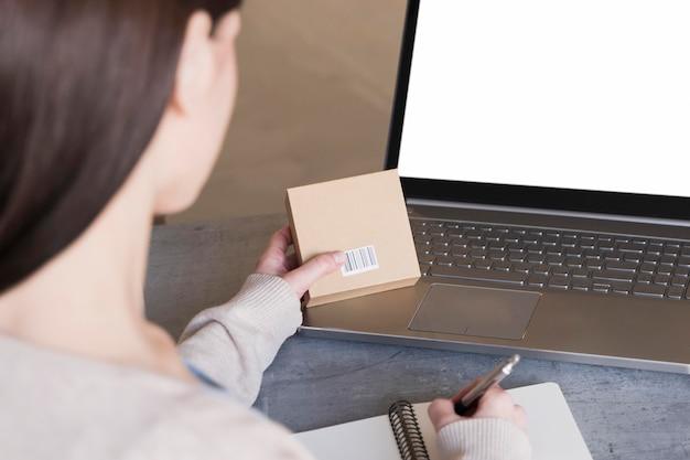 Wysoki kąt kobieta pracuje na laptopie i trzyma pudełko