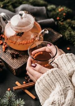 Wysoki kąt kobieta trzyma glsss z herbatą z rokitnika zwyczajnego
