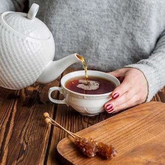 Wysoki kąt kobiety nalewania herbaty pojęcie