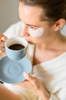 Wysoki kąt kobiety pije kawę z łatami do oczu