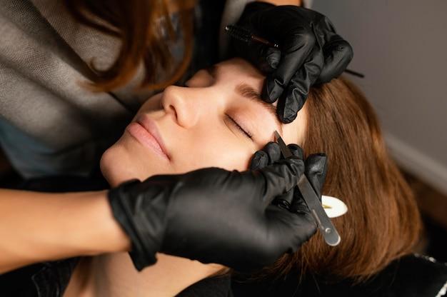 Wysoki kąt kosmetyczki wykonującej zabieg na brwi dla kobiety