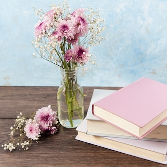 Wysoki kąt książek i kwiatów na drewnianym stole